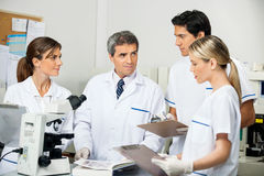 Scientist With Students Taking Notes In Laboratory. Mature male scientist with students taking notes in medical laboratory Royalty Free Stock Photography