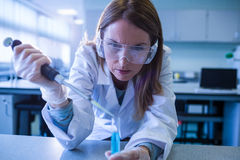 Scientist syringing chemical into test tube Stock Photo