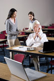 Scientist talking to assistants in conference room. Scientist in lab coat talking to assistants in conference room royalty free stock images
