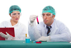 Scientist team in laboratory with blood tube. Two scientists working in laboratory,man examine blood tube and woman writing notes in clipboard Royalty Free Stock Photos