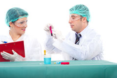 Scientist teamwok in laboratory. Team of two scientists people examine blood tube .Man pointing on tube and woman writing in clipboard Royalty Free Stock Images