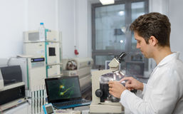 Scientist or tech with dark hair and brown eyes works with micro. Male scientist or tech with dark hair and brown eyes works with microscope samples in research Royalty Free Stock Image