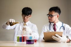 Scientist test liquid substrance in lab. Asian Scientist with lab coat dropping yellow liquid substance to test tube while guy writing result at chemical or stock images