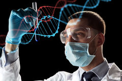 Scientist with test tube and dna molecule. Science, research and genetics concept - young scientist in safety glasses, face mask with test tube and virtual Royalty Free Stock Photos