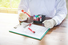 Scientist with test tube making research in clinical laboratory. Stock Photos