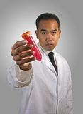 Scientist with Test Tube Radiant Gradient BG. Asian-American / Asian / Filipino model holding a test tube with red media, wearing a white lab coat and glasses Stock Photo