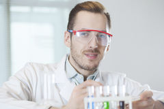 Scientist with test tubes in goggles Stock Image
