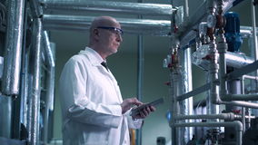 Scientist touching the valve. The person with the tablet touching the valve and continues the inspection stock footage