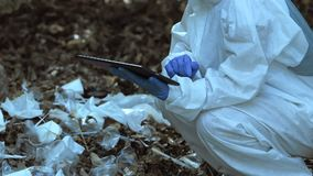 Scientist typing report about plastic dump in woods using tablet, soil pollution. Stock footage stock video
