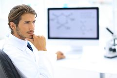 Scientist using computer and microscope in the laboratory Royalty Free Stock Photography