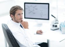Scientist using computer and microscope in the laboratory Stock Images