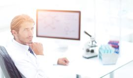 Scientist using computer and microscope in the laboratory Stock Photography