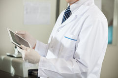 Scientist Using Digital Tablet In Laboratory. Midsection of male scientist using digital tablet in laboratory Stock Images