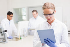 Scientist using tablet while colleagues working behind. In laboratory stock photos
