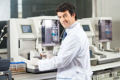 Scientist Using Urine Analyzer To Test Samples Stock Photos