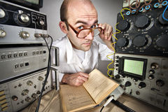 Scientist at vintage laboratory. Pensive scientist reading book at vintage technological laboratory Royalty Free Stock Image