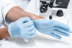 Scientist wearing protective gloves in chemical laboratory. Close-up partial view of scientist wearing protective gloves in chemical laboratory Stock Image
