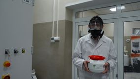 Scientist wearing protective suit and carrying a jar of toxic liquid inside a biohazard area Royalty Free Stock Photo