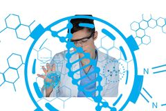 Scientist wearing safety glasses and a lab coat is working on a desk against DNA background royalty free stock photography