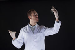 A scientist in a white coat on black background Royalty Free Stock Photos