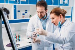 Scientist in white coats near board for notes having discussion during work. In lab stock photos