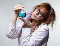 Scientist woman with blue liquid. On gray background Royalty Free Stock Photography