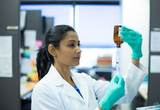 Scientist woman. Closeup portrait, smart woman scientist in white labcoat holding syringe needle and brown bottle in isolated lab background Royalty Free Stock Photos
