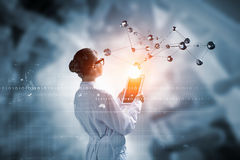 Scientist woman doing research. Mixed media Royalty Free Stock Image