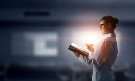 Scientist woman doing research. Mixed media. Attractive scientist woman with book in hands. Mixed media Royalty Free Stock Image