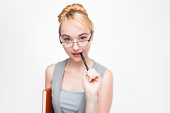 Scientist woman in glasses thinks of project ideas. Fair-haired scientist woman in glasses with book and pen thinking of new ideas about work project. Portrait Stock Photos