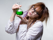 Scientist woman with green liquid. On gray background Stock Photo