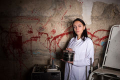 Scientist woman holding an aluminum box in front of a blood spla Stock Image
