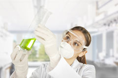 Scientist woman in lab coat with chemical glassware Stock Photo
