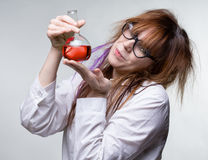 Scientist woman with red liquid. On gray background Stock Photos
