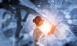 Scientist woman using tablet pc. Mixed media Stock Image