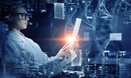 Scientist woman using tablet pc. Mixed media Stock Photography