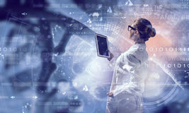 Scientist woman using tablet pc. Mixed media Royalty Free Stock Photography