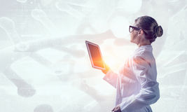Scientist woman using tablet pc. Mixed media . Mixed media Stock Image
