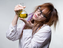 Scientist woman with yellow liquid. On gray background Stock Photos