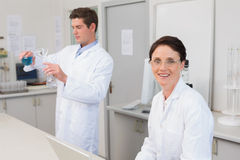Scientist working attentively with laptop and another with beaker Stock Photo