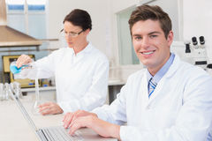 Scientist working attentively with laptop and another with beaker Royalty Free Stock Images