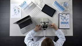 Scientist working on computer and microscope in laboratory, research top view stock photography
