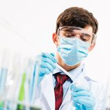 Scientist working in the lab. In protective mask, examines a test tube with liquid Stock Photo