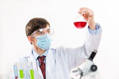 Scientist working in the lab. In protective mask, examines a test tube with liquid Stock Image