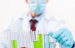 Scientist working in the lab. In protective mask and cap, examines a test tube with liquid Royalty Free Stock Photo