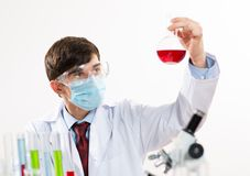 Scientist working in the lab. In protective mask, examines a test tube with liquid Stock Images