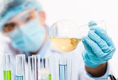Scientist working in the lab. In protective mask and cap, examines a test tube with liquid Royalty Free Stock Images