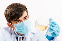 Scientist working in the lab. In protective mask, examines a test tube with liquid Royalty Free Stock Image