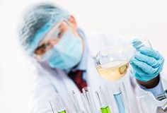 Scientist working in the lab. Examines a test tube with liquid Royalty Free Stock Photography