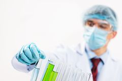 Scientist working in the lab. In protective mask and cap, examines a test tube with liquid Stock Image